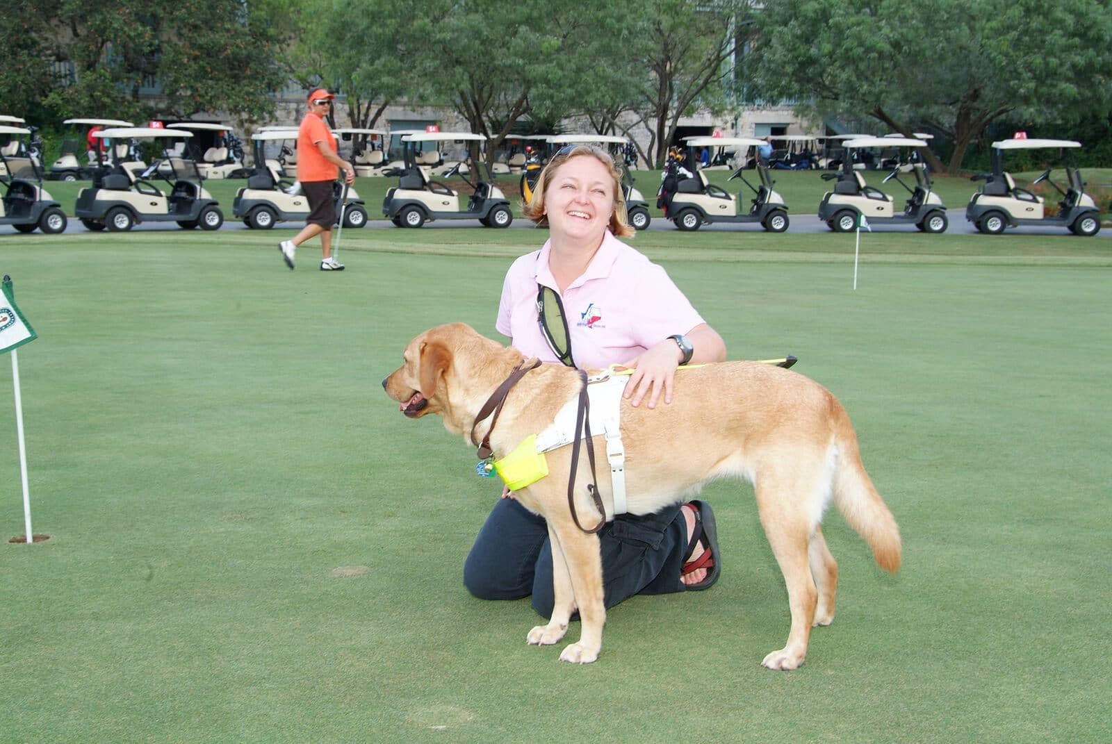 Guide Dog Instructor, Sandy, at a golf tournament with guide dog Autumn. Autumn is a yellow labrador with a white harness.