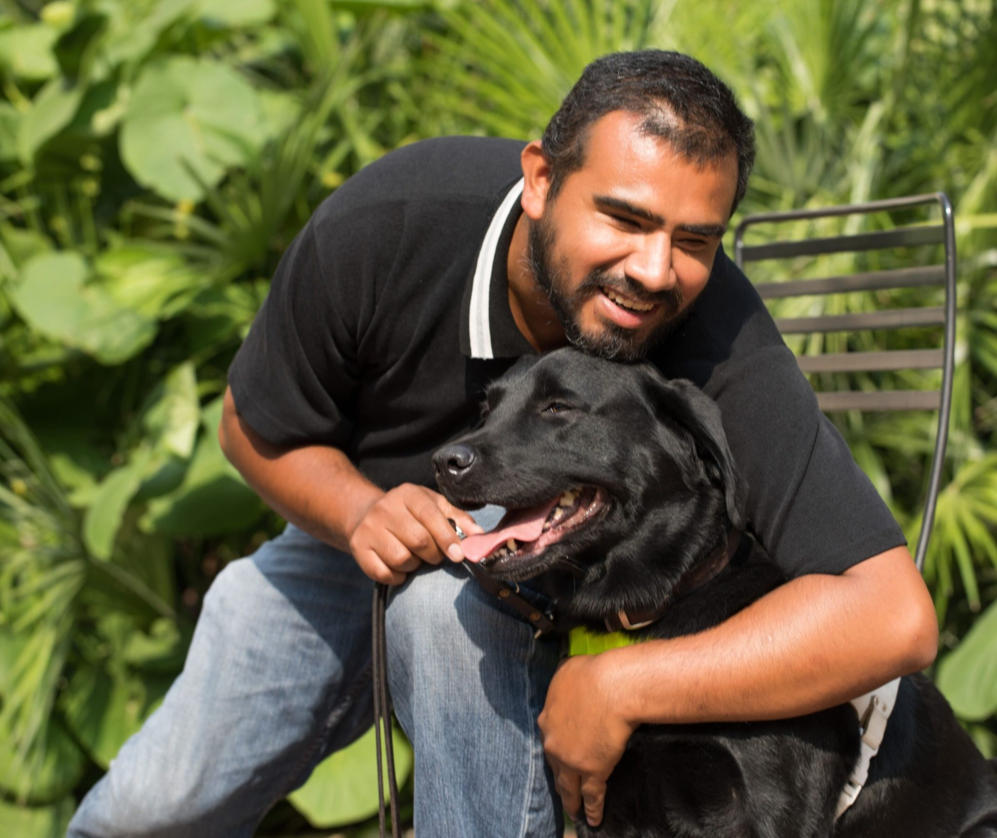 Guide Dog Owner, Pete smiling and hugging his guide dog Chance. This black labrador joyfully receives the affection!