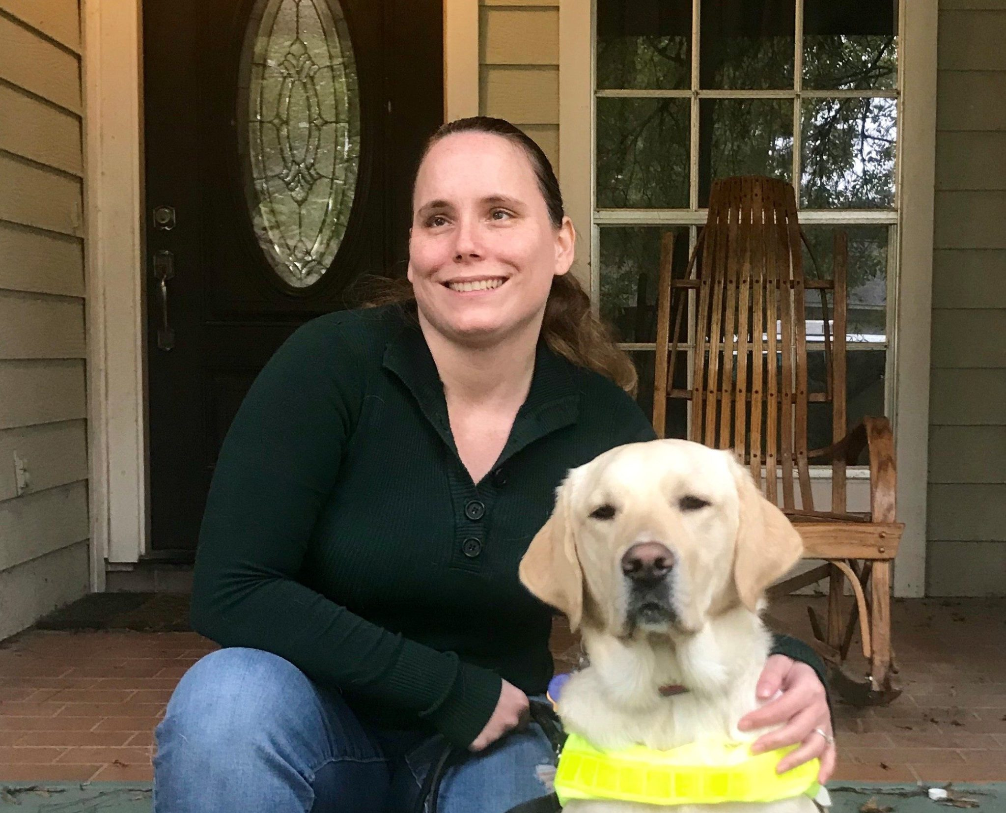 Image shows Guide Dog Owner Amanda sitting on the porch with her arm around her guide dog. Guide Dog Bell is a beautiful yellow lab. She's wearing her guide dog harness and is looking into the camera.